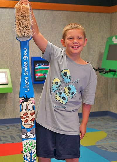 A young boy at the dentist standing next to a giant toy tooth brush